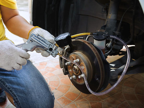 Mechanic bleeding the brakes of a car using a pistol grip vacuum bleeder with the tire and wheel of the car removed