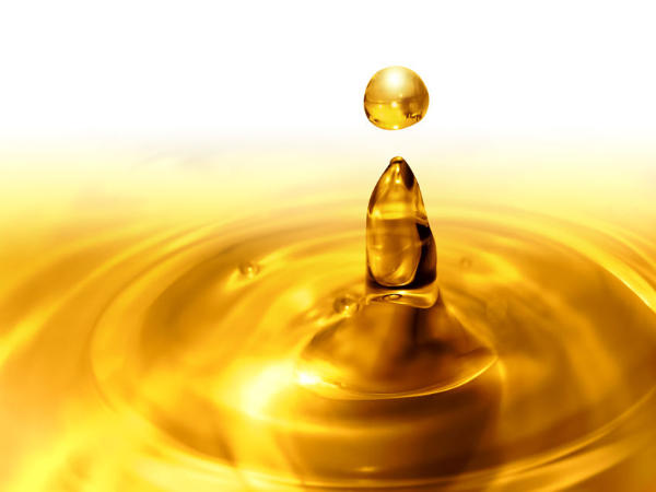 A drop of oil splashing onto a puddle of oil on a horizontal surface